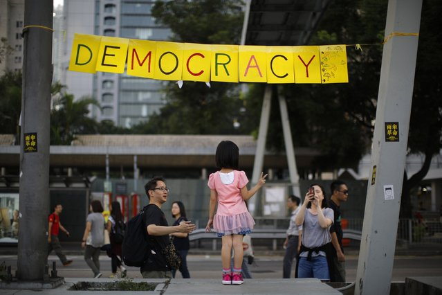 A girl poses next to a sign at an area blocked by pro-democracy protesters outside of the government headquarters building in Hong Kong October 11, 2014. Hundreds of student activists camped overnight at major protest sites in Hong Kong as the democracy movement sought to regather momentum after the government called off talks with its leaders aimed at defusing unrest in the global financial hub. (Photo by Carlos Barria/Reuters)