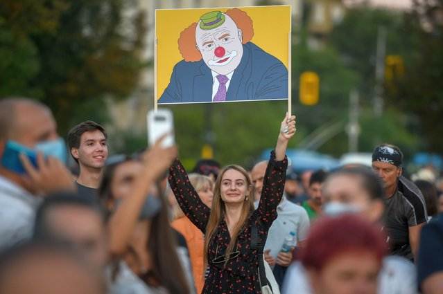 A woman holds a placard depicitng Bulgarian prime minister Boyko Borisov as a clown during an anti-government protest in Sofia, on July 20, 2020. Thousands of young people have been demanding for two weeks in Sofia for the resignation of the government which they accuse of protecting the oligarchy. Shaken by discontent that he did not see coming, Bulgarian leader Boyko Borissov is trying to save his skin at the head of the government after a decade of playing the balancing act between the interests of the great powers and the clans of oligarchs. (Photo by Nikolay Doychinov/AFP Photo)