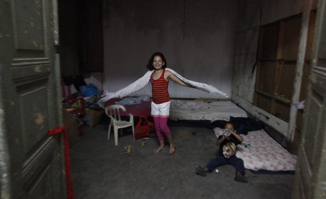 Siblings, who are children of members of Brazil's Movimento dos Sem-Teto (Roofless Movement), play in a vacant apartment in one of the 11 empty buildings that the movement took over recently, in the centre of Sao Paulo, November 6, 2012. According to City Hall, there are some 400,000 people in need of stable housing, including the 4,000 families of the Roofless Movement who are squatting in abandoned or vacant buildings that range from apartment blocks to hotels, in Sao Paulo, the largest city in South America. Picture taken November 6, 2012