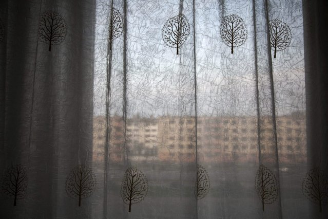 In this June 15, 2014 photo, an apartment block stands behind hotel room curtains on the main street in Hamhung, North Korea. (Photo by David Guttenfelder/AP Photo)