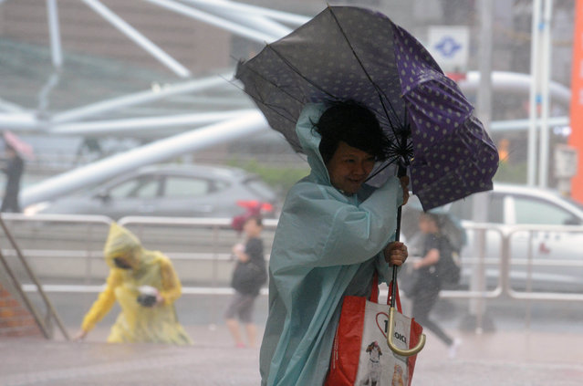 A woman uses an umbrella against strong wind and rain brought by typhoon Dujuan at Tamshui district, New Taipei City on September 28, 2015. More than 7,000 people were evacuated in Taiwan as 'super typhoon' Dujuan swirled towards the island, gathering strength as it bore down on the east coast. (Photo by Sam Yeh/AFP Photo)