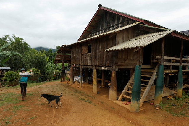 A man walks past a house standing on bombs dropped by the U.S. Air Force planes during the Vietnam War, in the village of Ban Napia in Xieng Khouang province, Laos September 3, 2016. (Photo by Jorge Silva/Reuters)