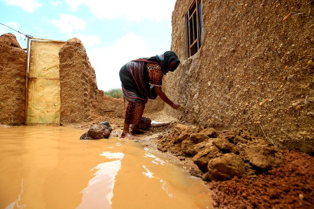 A Sudanese woman repairs damages to her house, after torrential rain lead to landslides and flash floods, in the town of Umm Dawan Ban, southeast of the capital Khartoum on August 2, 2020. (Photo by Ashraf Shazly/AFP Photo)