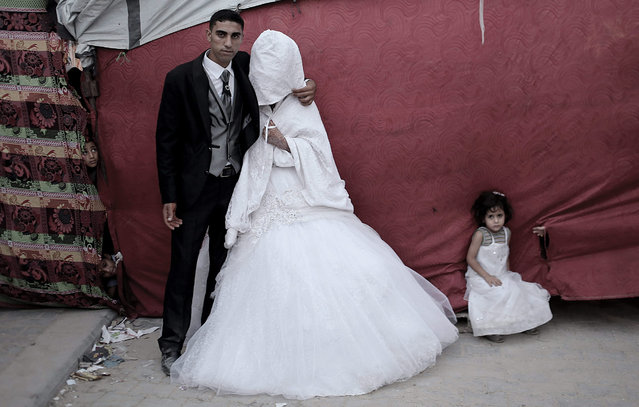 Palestinian groom Mohammed Yousef Al-Masri, 23, and his bride Zekriat Hamza Al-Masri, 20, pose for a picture next to their makeshift tent housing near their destroyed houses, which were damaged during the Israeli war against Gaza in the summer of 2014, during their wedding in Beit Hanun town in the northern Gaza Strip, 01 October 2015. More than 100,000 Palestinians remain homeless one year after the 2014 summer's Israeli-Gaza war. (Photo by Mohammed Saber/EPA)