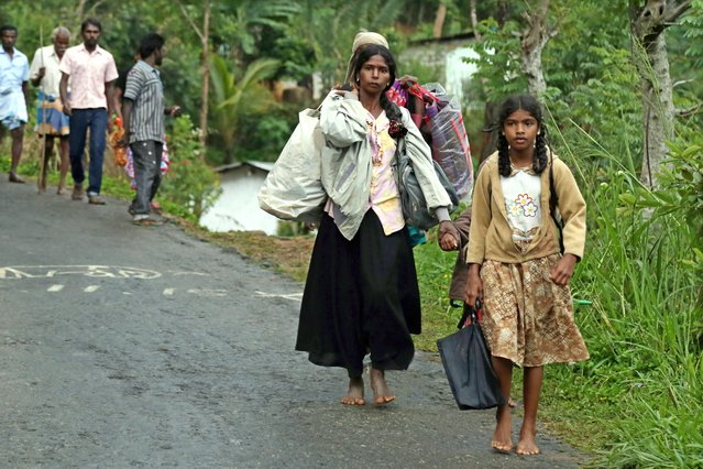 Landslide affected Sri Lankans evacuating the area with their families and belongings at Meeriyabedda, Haldummulla in Badulla 218 kms towards the interior from Colombo, Sri Lanka, 29 October 2014. (Photo by M. A. Pushpa Kumara/EPA)
