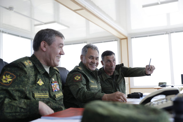 Russian Defense Minister Sergei Shoigu, center, the head of General Staff, Gen. Valery Gerasimov, left, and the head of the main directorate of combat training Lieutenant-General Ivan Buvaitsev head an operation during military drills at the Black Sea coast, Crimea, Friday, September 9, 2016. Russia has deployed cruise missiles, multiple rocket launchers, tanks and its latest anti-aircraft system at massive military drills in Crimea. The drills which began across southern Russia and Crimea earlier this week and involve over 120,000 troops are some of the largest exercises Russia has held for years. (Photo by Pavel Golovkin/AP Photo)