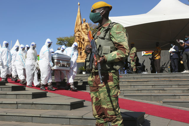 An armed soldier stands guard during the burial of a Zimbabwean minister Perence Shiri, who died of Covid-19, in Harare, Friday, July, 31, 2020. Zimbabwe's capital, Harare, was deserted Friday, as security agents vigorously enforced the country's lockdown amidst planned protests. (Photo by Tsvangirayi Mukwazhi/AP Photo)