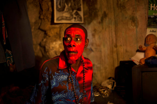 In this January 27, 2013 photo, snake handler Saintilus Resilus, with his face painted red, talks to his assistants as they get ready to perform during pre-Lenten Carnival season in Petionville, Haiti. Resilus sees himself as something of a performance artist, showing off with snakes and other animals that Haitians don't see every day, earning tips from impromptu audiences. (Photo by Dieu Nalio Chery/AP Photo/Matt Dayhoff)