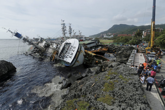 People view sinking fishing vessels caused by super typhoon Meranti in Kaohsiung city, southern Taiwan, 15 September 2016. Typhoon Meranti is moving towards the Chinese provinces of Fujian and Zhejiang after lashing southern part of Taiwan on 14 September, leaving close to a million households without power and water supplies. (Photo by Ritchie B. Tongo/EPA)