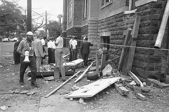A civil defense worker and firemen walk through debris from an explosion which struck the 16th street Baptist Church, killing four girls and injuring 22 others, in Birmingham, Alabama, on September 15, 1963. The open doorway at right is where the girls are believed to have died. The horrific attack rallied public support to the cause of civil rights. Four men, members a Ku Klux Klan group, were responsible for planting a box of dynamite under the steps of the church. Three of the four were eventually tried and convicted. (Photo by AP Photo)