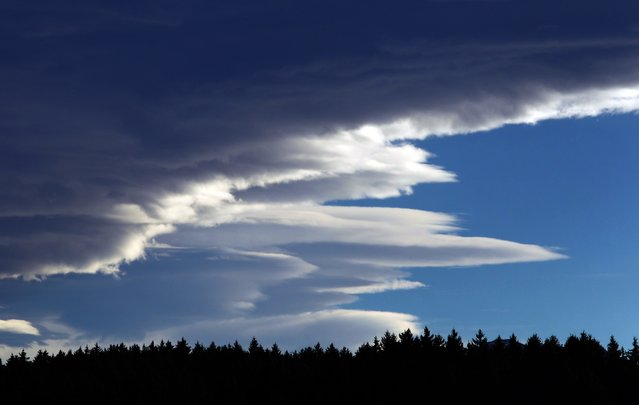 Foehn clouds float over a forest of the alpine upland near Seeg, southern Germany, on November 11, 2014. Foehn is a dry and warm down-slope wind occuring in the lee of a mountain range. (Photo by Karl-Josef Hildenbrand/AFP Photo)
