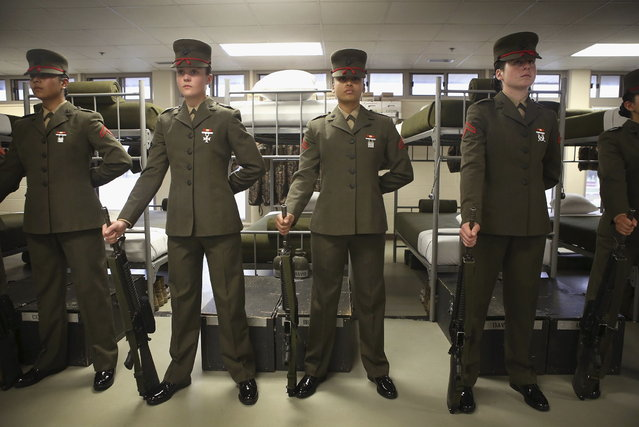 Female Marine recruits stand for inspection near the end of their stay at boot camp on February 26, 2013 at MCRD Parris Island, South Carolina. Female enlisted Marines have gone through recruit training at the base since 1949. About 11 percent of female recruits who arrive at the boot camp fail to complete the training, which can be physically and mentally demanding. On January 24, 2013 Secretary of Defense Leon Panetta rescinded an order, which had been in place since 1994, that restricted women from being attached to ground combat units. (Photo by Scott Olson/AFP Photo)