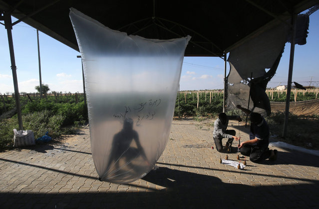 Palestinians inflate plastic bags before being attached with incendiary devices and flown towards Israel, near Rafah along the border between the Gaza Strip and Israel on August 21, 2020. (Photo by Said Khatib/AFP Photo)