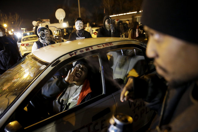 Protesters chant in front of the Ferguson Police Department, Tuesday, November 25, 2014, in Ferguson, Mo. Missouri's governor ordered hundreds more state militia into the St. Louis suburb, Tuesday after a night of protests and rioting over a grand jury decision's not to indict police officer Darren Wilson in the killing of Michael Brown, a case that has inflamed racial tensions in the U.S. (Photo by David Goldman/AP Photo)
