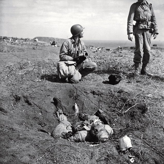 American troops chat near a dead Japanese soldier on Iwo Jima. The degree to which the Japanese were willing to fight to the death, rather than surrender, is summed up in one remarkable statistic: Close to 20,000 Japanese soldiers were killed during the battle; only around 200 were captured. (Photo by W. Eugene Smith/Time & Life Pictures)