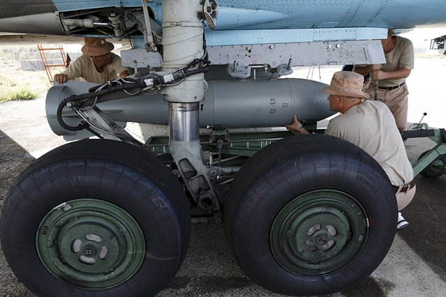 Russian ground staff members load a Sukhoi Su-34 fighter jet with weapons at the Hmeymim air base near Latakia, Syria, in this handout photograph released by Russia's Defence Ministry October 22, 2015. (Photo by Reuters/Ministry of Defence of the Russian Federation)