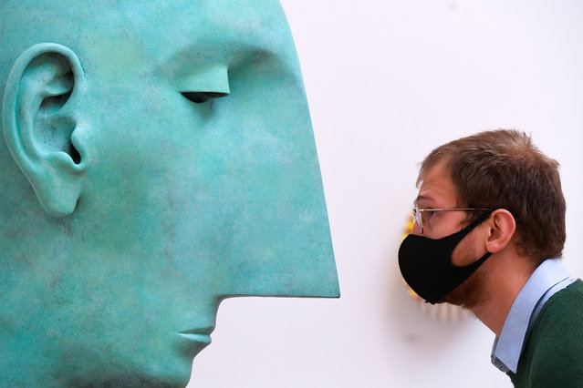 """A member of staff looks at """"Head II"""" by Tim Shaw at a preview for the 'summer' exhibition at the Royal Academy of Arts in London on September 28, 2020. The 252nd Summer Exhibition was postponed because of the coronavirus pandemic and will take place in the autumn for the first time. (Photo by Kirsty O'Connor/PA Images via Getty Images)"""