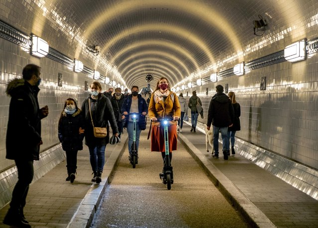 People wear face masks as they ride an E-scooter in the Old Elbe Tunnel in Hamburg, Germany, Thursday, October 15, 2020. To avoid the spread of the coronavirus the use of a face mask in the 117-year-old tunnel under the Elbe river is mandatory. (Photo by Michael Probst/AP Photo)