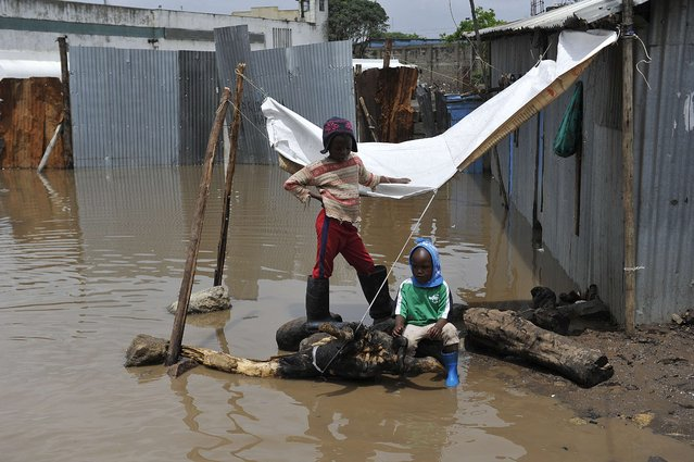 Two boys sit outside their flooded house at the Mukuru Kwa Njenga slum following heavy rainfall October 29, 2015, in the capital Nairobi. According to the weather forecast, the El Nino weather phenomenon is expected to hit Kenya, but says it is unlikely to unleash the fury and destruction of 1997. (Photo by Simon Maina/AFP Photo)