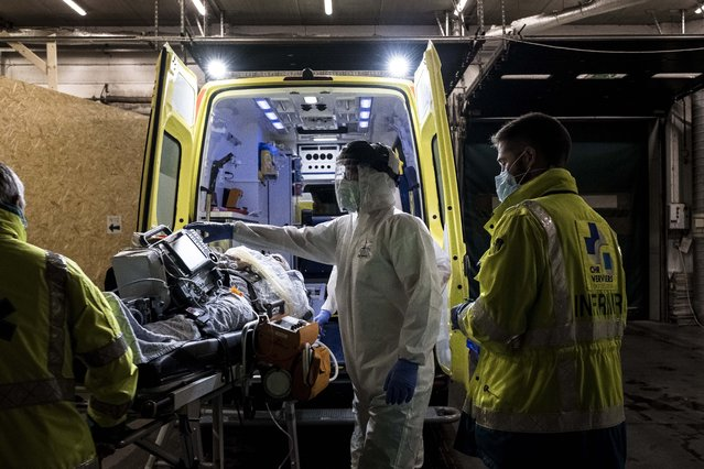 Ambulance crew work as a patient arrives at the CHR CItadelle hospital in Liege, Belgium, Thursday, October 29, 2020. Belgium has announced restrictive measures across the country in an effort to curb the fast-rising tide of COVID-19, coronavirus cases. (Photo by Valentin Bianchi/AP Photo)