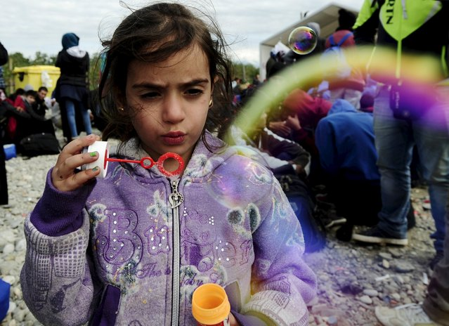 A migrant child blows soap bubbles at a transit camp in Gevgelija, Macedonia, after entering the country by crossing the border with Greece, September 29, 2015. (Photo by OgnenTeofilovski/Reuters)