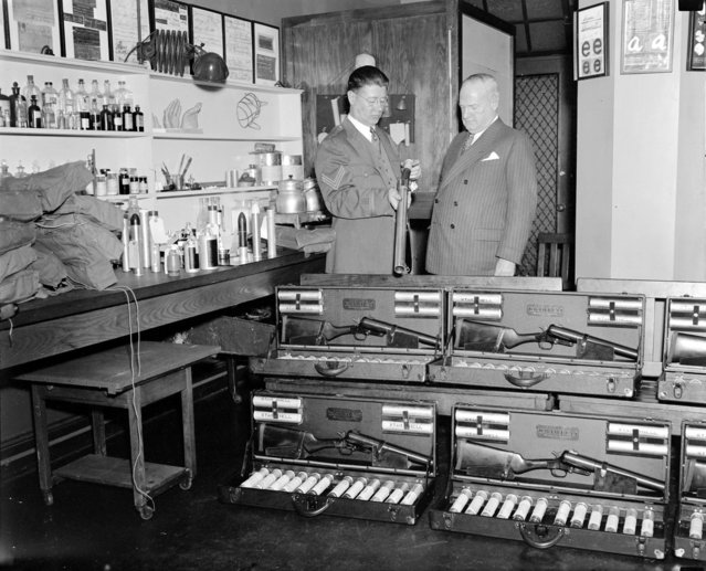Inspecting new riot guns at police headquarters, 1936. (Photo by Leslie Jones)