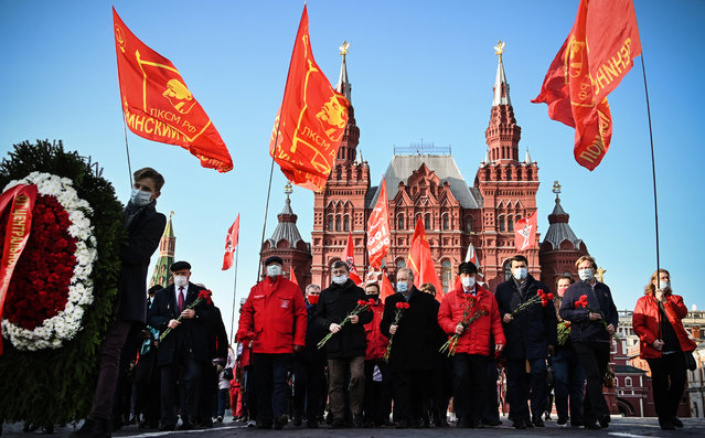 Russian Communist supporters march towards the Mausoleum of Vladimir Lenin to lay flowers on the 102nd anniversary of the Komsomol on Red Square in Moscow on October 28, 2020. Komsomol, The All-Union Leninist Young Communist League, was a political youth organisation in the Soviet Union, the youth division of the Soviet Communist Party,  established in 1918 and died shortly after the collapse of the Soviet Empire in 1991. (Photo by Alexander Nemenov/AFP Photo)