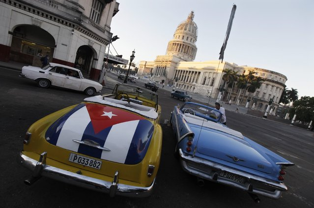 A car with a Cuban flag is parked near Cuban Capitol in Havana December 18, 2014. Cuban President Raul Castro hailed a landmark exchange of prisoners with the United States on Wednesday and praised U.S. President Barack Obama as the two countries agreed to normalize relations after more than five decades of hostility. (Photo by Enrique De La Osa/Reuters)