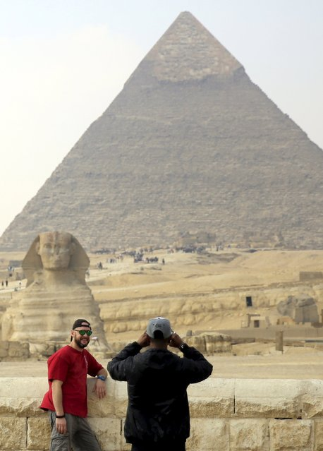 A tourist takes a picture in front of the Sphinx at the Giza Pyramids on the outskirts of Cairo, Egypt, November 8, 2015. (Photo by Amr Abdallah Dalsh/Reuters)