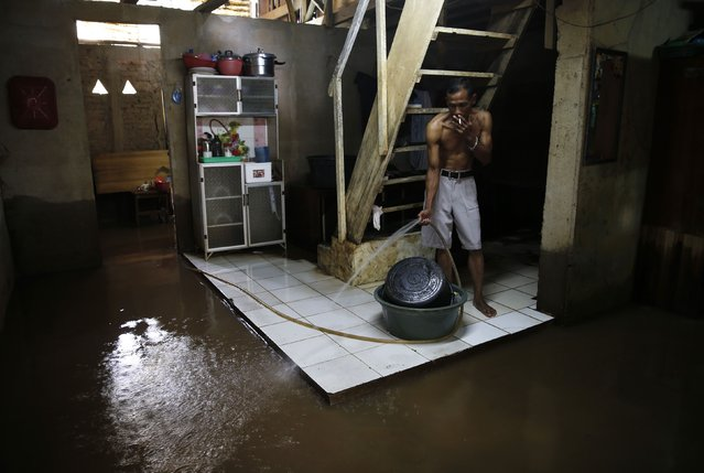 A man sprays water to clean his flooded house of mud at Kampung Melayu residential area in Jakarta, December 23, 2014. (Photo by Reuters/Beawiharta)