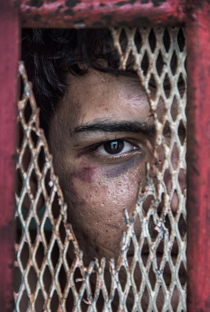 Iraqi asylum seeker Abdullatif Almoftaji stares through the wire of a police cell in the town of Lorengau, Manus Island in Papua New Guinea. Abdullatif was 17-years-old when he was first detained trying to enter Australia three years ago. He is pictured here in jail, having been arrested for allegedly trying to steal food while drunk, among other things. Cassey made the image through a hole in the cell wire. Later police caught Cassey trying to pass Abdullatif food and clothes and threatened to lock him up too. (Photo by Brian Cassey/The Walkley Foundation)