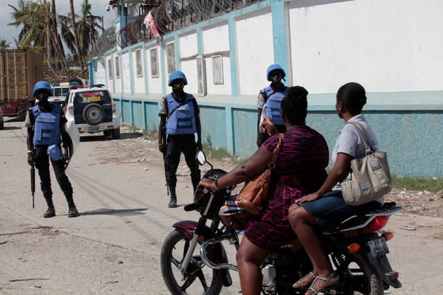 Peacekeepers stand in front of vehicles as they secure the perimeter of the MINUSTAH base after Hurricane Matthew in Les Cayes, Haiti, October 15, 2016. (Photo by Andres Martinez Casares/Reuters)
