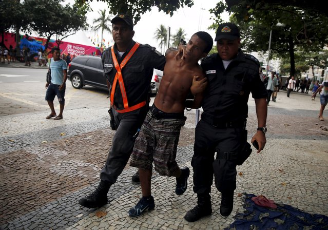A man suspected of being a thief is escorted by police officers during the LGBT Pride Parade in Copacabana beach in Rio de Janeiro, Brazil, November 15, 2015. (Photo by Pilar Olivares/Reuters)