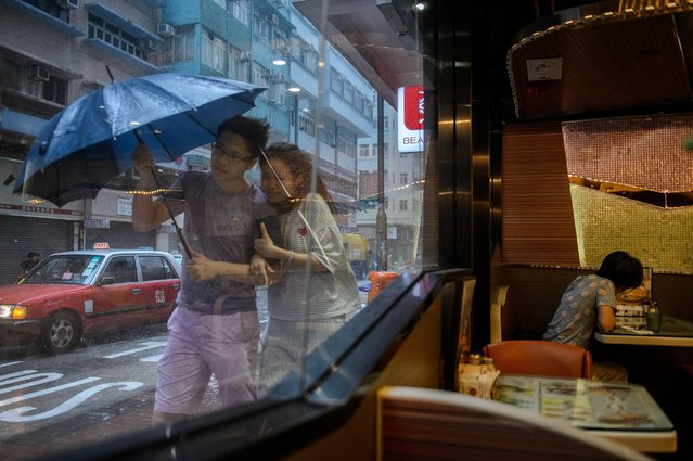 A couple walks in the heavy rain as Typhoon Haima makes landfall in Hong Kong, October 21, 2016. (Photo by Anthony Wallace/AFP Photo)