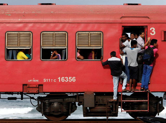 Commuters hang off a local passenger train in the morning in Colombo, Sri Lanka September 8, 2016. (Photo by Dinuka Liyanawatte/Reuters)