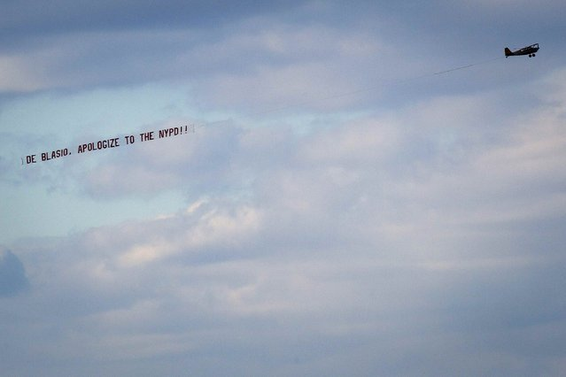 "An airplane towing a banner reading ""De Blasio, apologize to the NYPD"" flies over the Hudson River in New York December 31, 2014. Police union leaders said their grievances with New York City Mayor Bill de Blasio remained unresolved after meeting with him on Tuesday, 10 days after they said he was partly to blame for a gunman's deadly attack on two policemen. (Photo by Carlo Allegri/Reuters)"