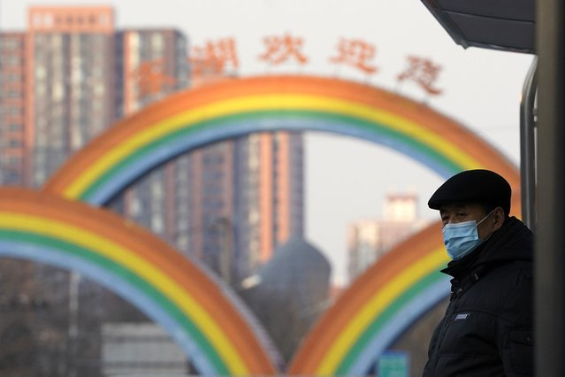 A resident wearing a mask to protect from the coronavirus waits at a bus stop near rainbow decorations on the streets of Beijing on Sunday, December 27, 2020. Beijing has urged residents not to leave the city during the Lunar New Year holiday in February, implementing new restrictions and mass testings after several coronavirus infections last week. (Photo by Ng Han Guan/AP Photo)