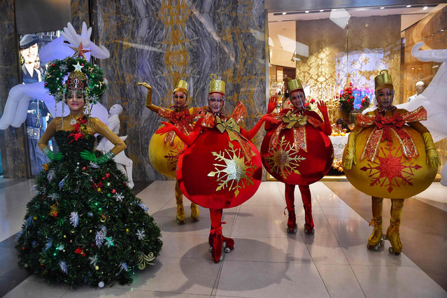 Models and dancers dressed as Christmas trees and baubles while wearing face shields put on a display for shoppers in a shopping mall in Bangkok in December 24, 2020. (Photo by Lillian Suwanrumpha/AFP Photo)