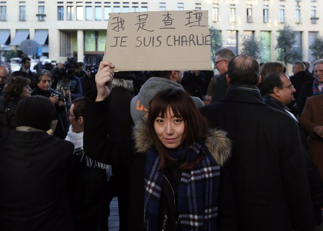 """A woman holds a sign that reads, """"I am Charlie"""" in Chinese and French, during a protest against terrorism, and in solidarity with the victims of a shooting by gunmen at the Paris offices of the satirical weekly newspaper Charlie Hebdo earlier this week, in Beirut January 11, 2015. (Photo by Jamal Saidi/Reuters)"""
