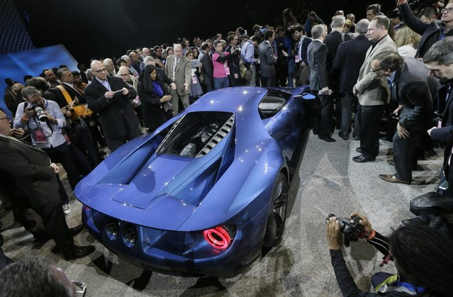Journalists surround the new Ford GT after it was unveiled at the North American International Auto Show, Monday, January 12, 2015 in Detroit. (Photo by Carlos Osorio/AP Photo)
