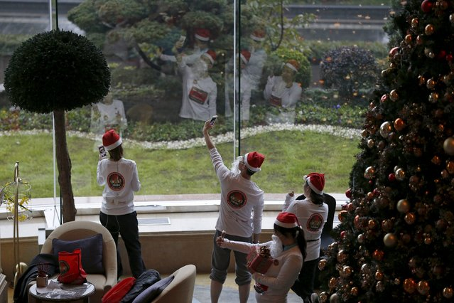 Runners dressed in Santa outfits take selfies before a charity Santa run in Shanghai, China, November 29, 2015. (Photo by Aly Song/Reuters)