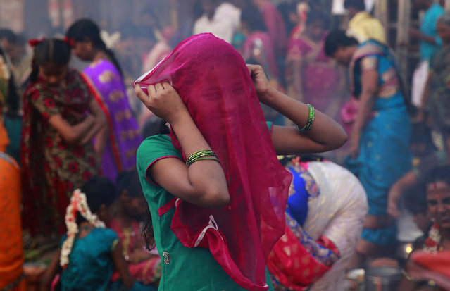A Tamil Hindu girl covers her face with a scarf to keep out smoke, as women cook special food to celebrate the harvest festival of Pongal at Dharavi, one of the world's largest slums, in Mumbai, India, Thursday, January 15, 2015. (Photo by Rafiq Maqbool/AP Photo)