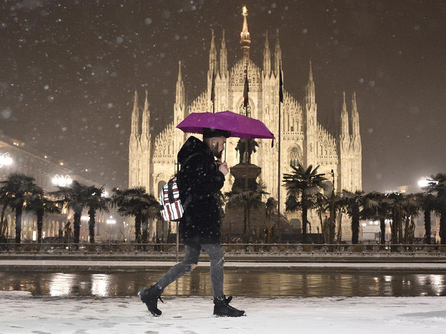 A man walks at Duomo square covered in snow, with backdrop of Milan Cathedral, in Milan, Italy, 01 March 2018. The wave of snow and freezing temperatures that has hit Italy continued to cause disruption in many parts of the country, especially affecting the transport sector. (Photo by Flavio Lo Scalzo/EPA/EFE)