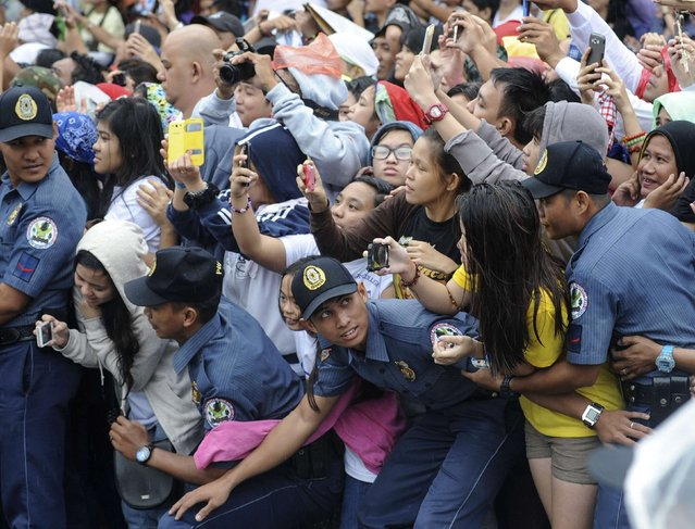 Members of the Philippine National Police prevent well-wishers from moving forward as Pope Francis' motorcade passes by in Manila January 18, 2015. (Photo by Ezra Acayan/Reuters)