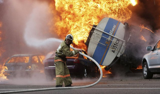A firefighter tries to extinguish a fire after a road accident in downtown Almaty, on Thursday, June 27, 2013. A multi-story apartment building caught fire in the center of Almaty, Kazakhstan after a road accident,  on Thursday, June 27. According to witnesses, the fire is a result of a petrol tank lorry that  exploded near Rixos hotel at the crossing killing one person and destroying 20 apartments. (Photo by Sergey Khodanov/AP Photo)
