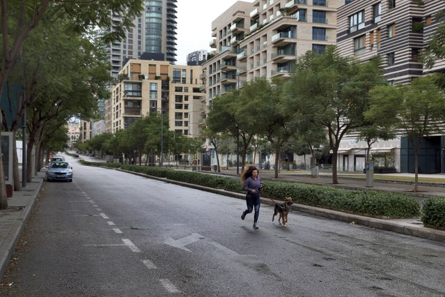 A woman runs with her dog in an almost empty street during a lockdown aimed at curbing the spread of the coronavirus, in Beirut, Lebanon, Thursday, January 14, 2021. Lebanese authorities began enforcing an 11-day nationwide shutdown and round the clock curfew Thursday, hoping to limit the spread of coronavirus infections spinning out of control after the holiday period. (Photo by Bilal Hussein/AP Photo)