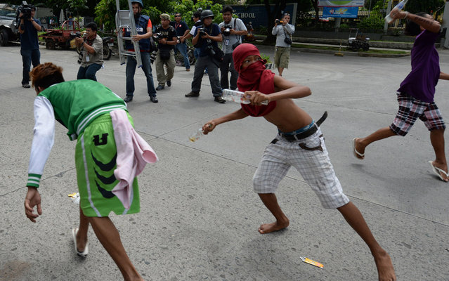 Informal settlers throw bottles at policemen (not pictured) during a clash in Manila on July 1, 2013 after residents blocked a road in anticipation of the demolition of their homes. Philippine informal settlers hurling rocks, improvised explosives and human refuse fought running street battles with riot police on July 1 around a sprawling Manila shantytown that is set for redevelopment. (Photo by Ted Aljibe/AFP Photo)
