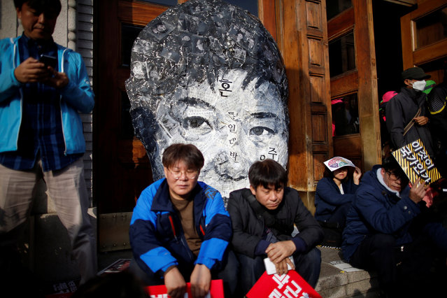 People sit in front of a giant cut-out of President Park Geun-hye during a rally calling for President Park Geun-hye to step down in central Seoul, South Korea, November 12, 2016. (Photo by Kim Hong-Ji/Reuters)
