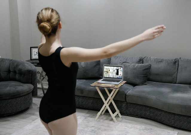 14 years old Duru Suyece practices ballet in their house's living room during her online ballet class due to the coronavirus (Covid-19) pandemic in Izmir, Turkey on January 28, 2021. (Photo by Omer Evren Atalay/Anadolu Agency via Getty Images)