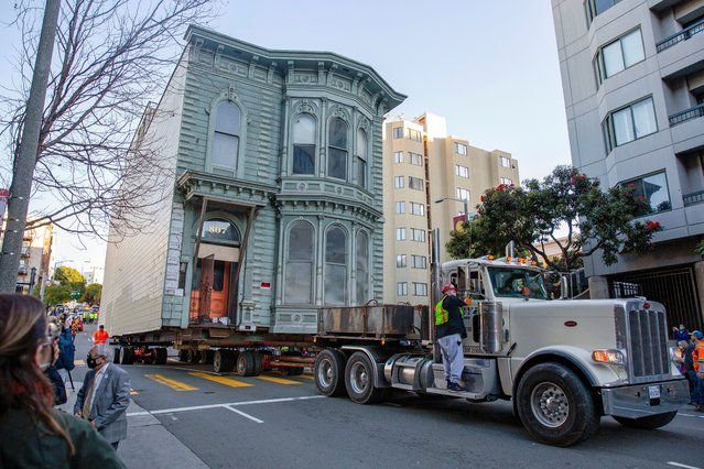 The 139-year-old Victorian house known as the Englander House is hoisted on a flat bed and pulled down Franklin Street towards its new location six blocks away, as the original site is to be used to build a 48-unit, eight-story apartment building, in San Francisco, California, U.S. February 21, 2021. (Photo by Brittany Hosea-Small/Reuters)